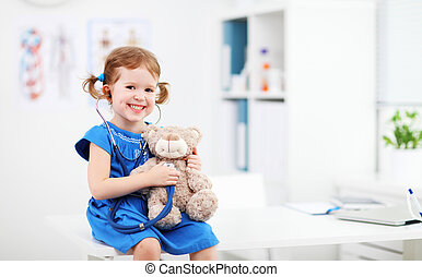 Child girl playing doctor with teddy bear