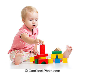 Child girl playing toy blocks and building tower. Isolated...