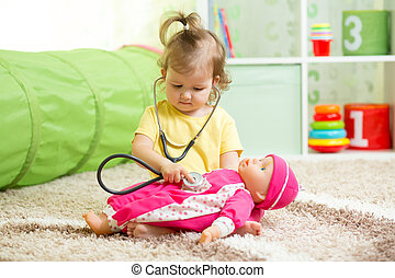 Child Girl Playing With A Doll In Playroom