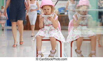 Child girl playing with a mobile phone in the shopping mall. Baby uses a game application on a smartphone