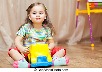 Child girl playing with a toy car on floor