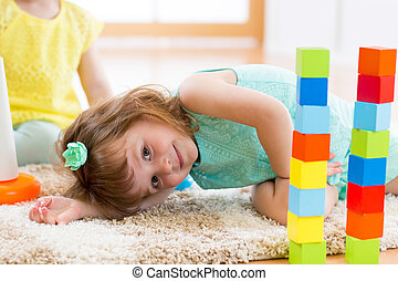 child girl playing with block toys on floor