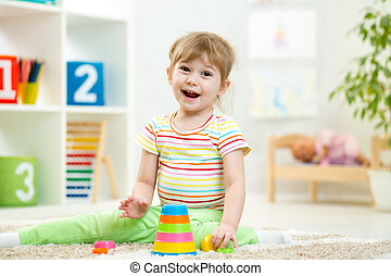 child girl playing with colorful toys