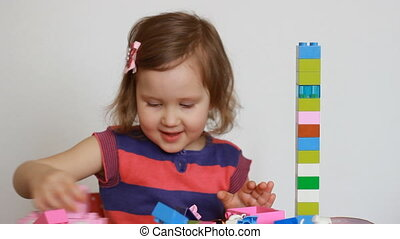 Child girl playing with colourful blocks of a constructor....