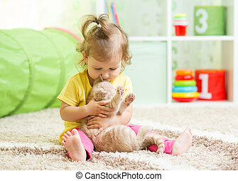 Child girl playing with her cat kitten on the floor