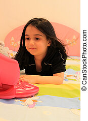 Child girl playing with laptop