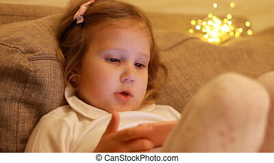 Child girl playing with smartphone. Baby watching video on mobile phone on the background of lights boke.