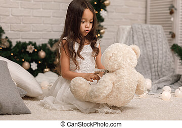child girl playing with teddy bear near the Christmas tree