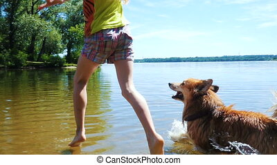 child girl playing with the dog at the river
