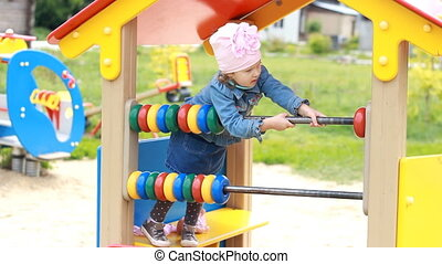 Child girl plays in the playground in different games....