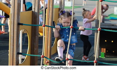 Child girl plays in the playground in different games in the...