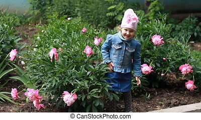 Child girl poses for a photo as a model and dances in the peony garden.