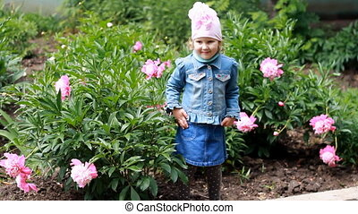 Child girl poses for a photo as a model in the garden with peonies.