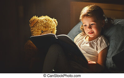 child girl reading a book in bed