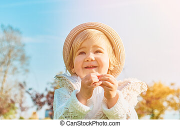 Child girl rejoices on a walk in the park on a sunny day