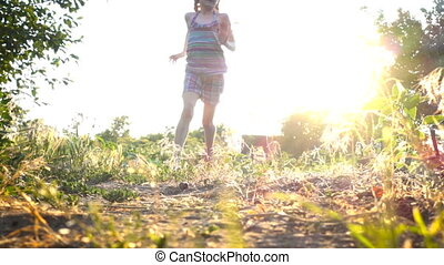 child girl running on the ground with bare feets at the sunset time