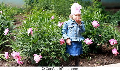Child girl send air kisses. Garden with peonies and funny...