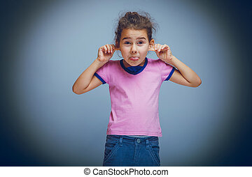 child girl showing tongue pulls ears on gray background...