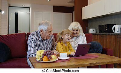 Child girl shows something in laptop to grandparents, seniors couple learning how to use computer