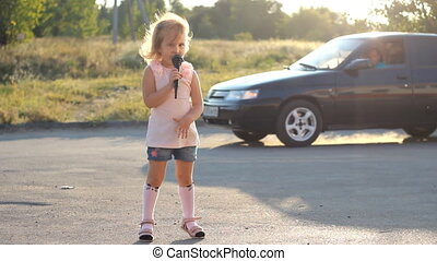 Child girl sings into a microphone a song in the rays of a...