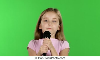 Child girl sings the song into the microphone. Green screen
