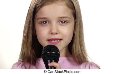 Child girl sings the song into the microphone. White background. Close up. Slow motion