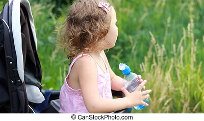 Child girl sits in a baby carriage and drinks water from a bottle.