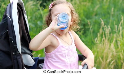 Child girl sits in a baby stroller and drinks water from a bottle.