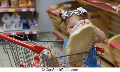 Child girl sits in a trolley for food in the supermarket and...