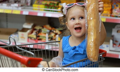 Child girl sits in a trolley for products in the store and...