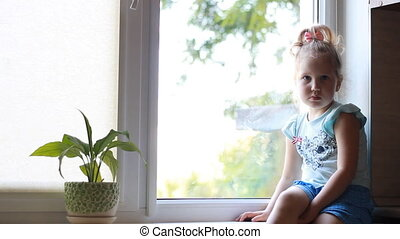 Child girl sits on a window sill and looks out the window.