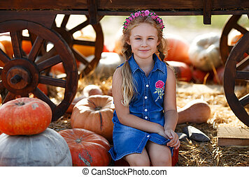 Child girl sitting between pumpkins at local farmer market in sunny autumn day