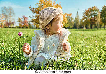 Child girl sitting in grass with clover in hand in autumn