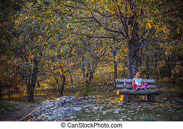 Child girl sitting in the middel of the forest, Extremadura, Spain