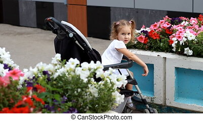 Child girl sitting in the stroller on a walk with mom in the park with beautiful flowers