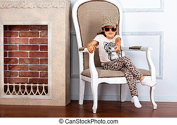 Child girl sitting on a chair near fireplace.