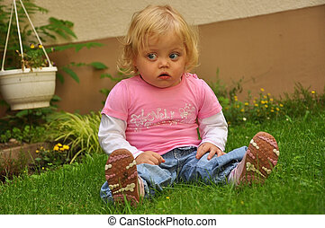 Child girl sitting on the grass