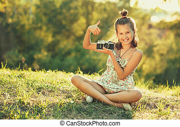 Child girl sitting on the grass. In her hands she has an old photo camera and she shows gesture all right