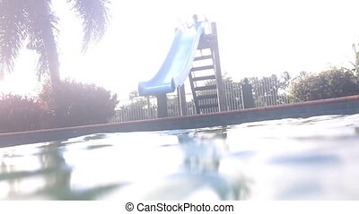 Child girl slide and dive underwate - Slow motion of a young...