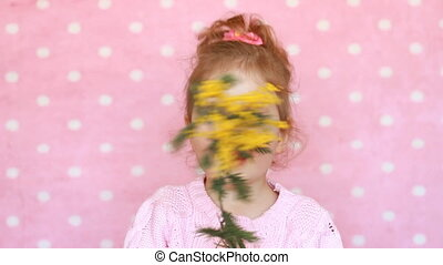 Child girl sniffs of a mimosa flower and sneezes. Allergy to...