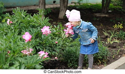 Child girl sniffs the aroma of peony flowers and sneezes. Children's allergies