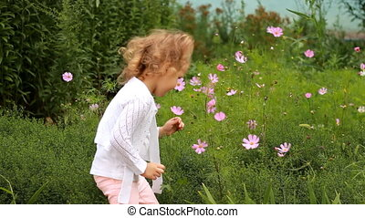 Child girl sniffs the scent of flowers in the garden on a windy summer day