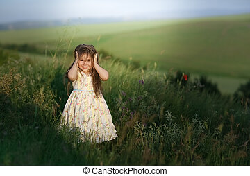 Child girl stands in a summer field with high green grass