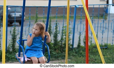 Child girl swings on a swing in the playground