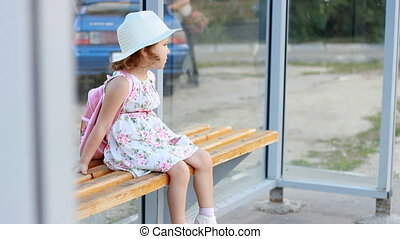 Child girl tourist in a hat and with a backpack is sitting...