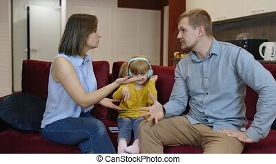 Caucasian child girl kid trying to be distracted and not hear quarrels between parents at home. Angry man and woman quarrelling and fighting in living room. Family problems conflict, crisis. Parenting