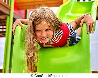 Child girl upside down on playground .