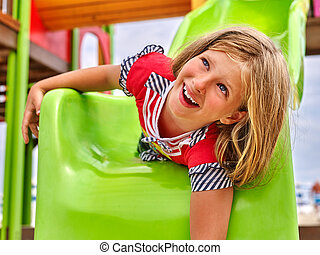 Child girl upside down slippery dip on playground .