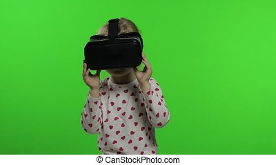 Child teen girl using VR app headset helmet to play simulation game, drawing. Watching virtual reality 3d 360 video. Isolated on chroma key green background in studio. Kid in VR goggles looking around