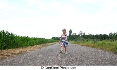 Child girl walking along a rural road.